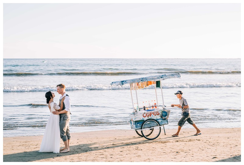 Bride and groom kissing on the beach with a Copos vender during golden hour after their beach elopement in Samara Costa Rica. Photographed by Kristen M. Brown, Samba to the Sea Photography.