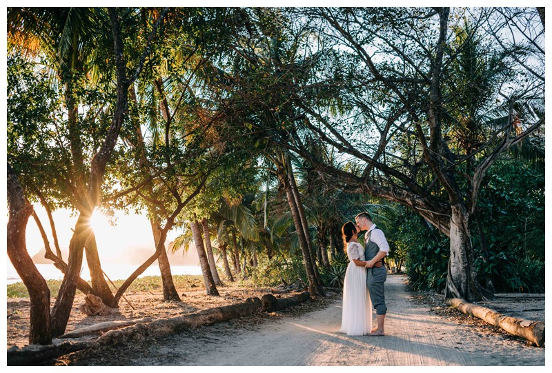 Bride and groom kissing under palm trees during golden hour after their beach elopement in Samara Costa Rica. Photographed by Kristen M. Brown, Samba to the Sea Photography.