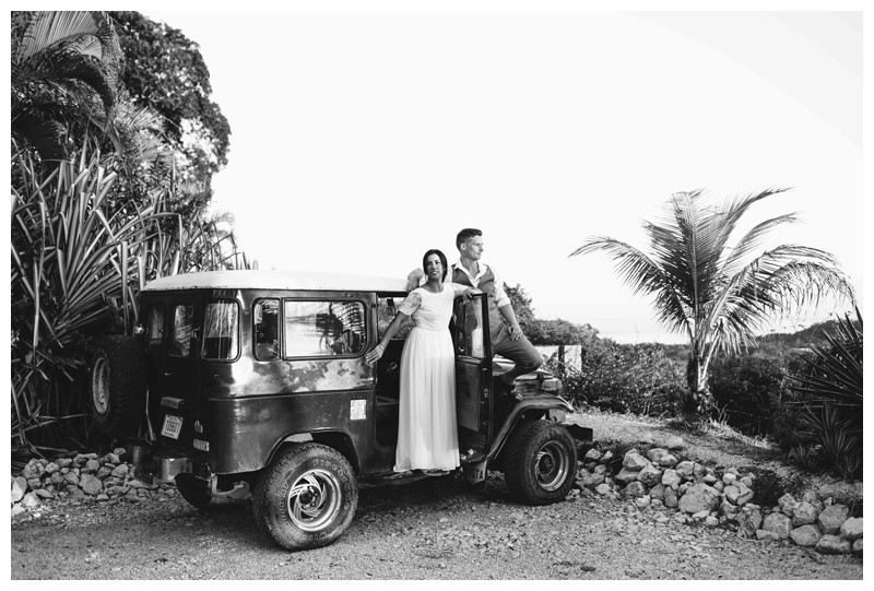 Bride and groom standing on a Toyota Land Cruise J40 after their beach elopement in Samara Costa Rica. Photographed by Kristen M. Brown, Samba to the Sea Photography.