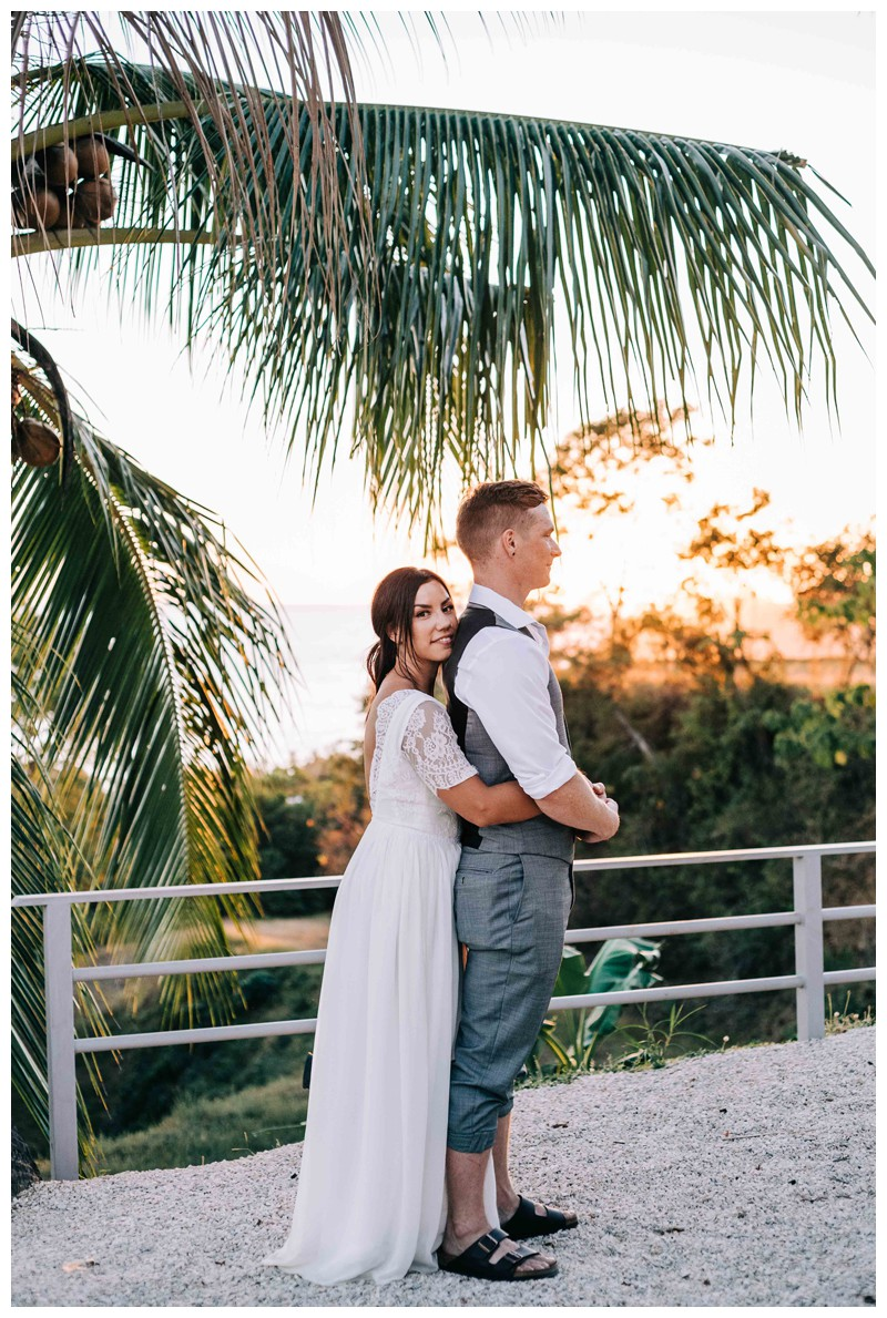 Bride and groom standing under palm trees during golden hour after their beach elopement in Samara Costa Rica. Photographed by Kristen M. Brown, Samba to the Sea Photography.