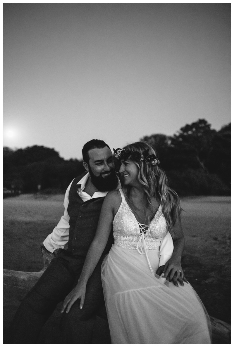 Bride and groom kissing on the beach as the full moon rises after their Costa Rica elopement. Elope to Tamarindo Costa Rica. Photographed by Kristen M. Brown, Samba to the Sea Photography.