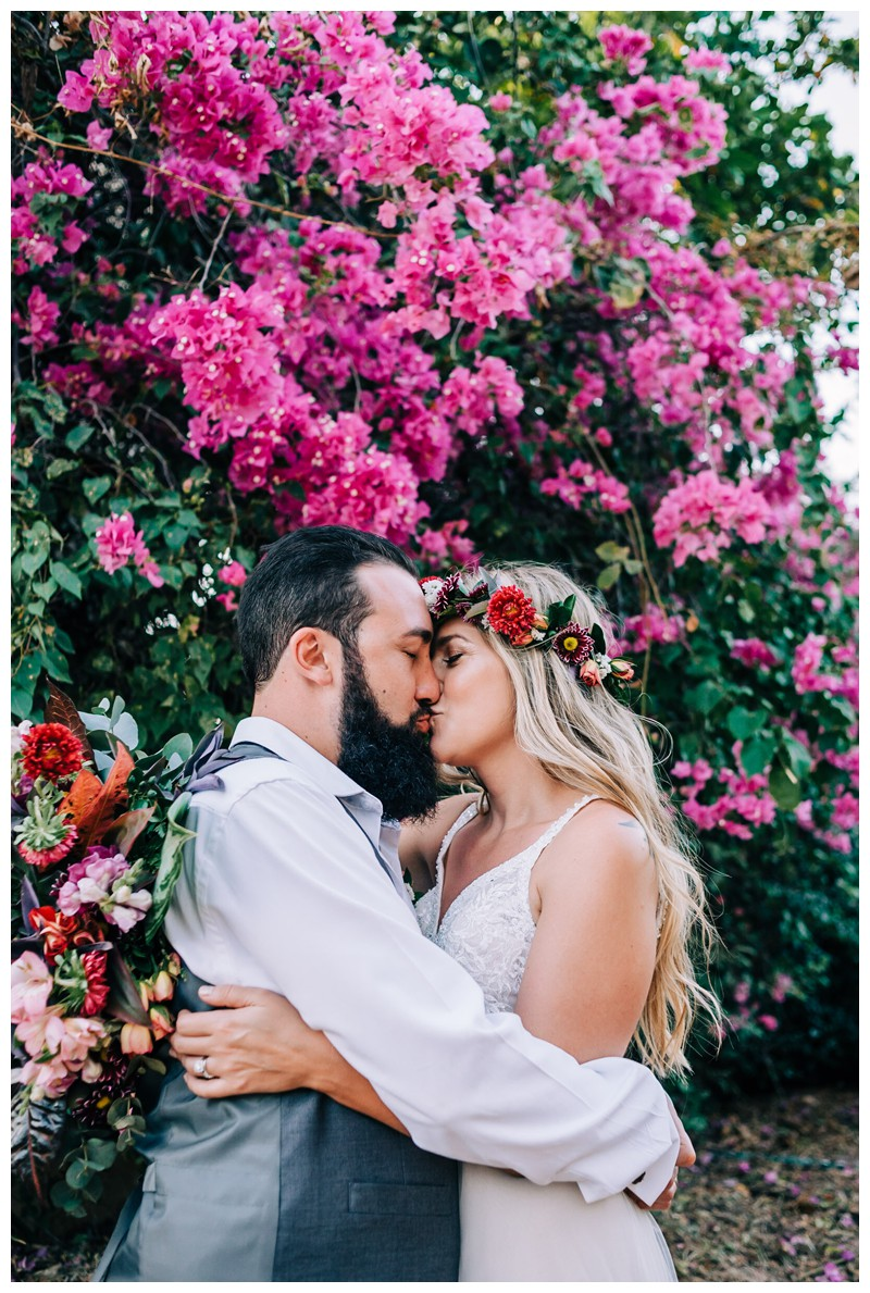Bride and groom kissing in front a gorgeous magenta Bougainvillea bush. Elope to Tamarindo Costa Rica. Photographed by Kristen M. Brown, Samba to the Sea Photography.