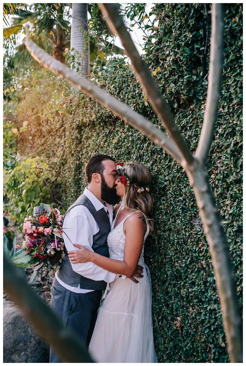 Bride and groom romantically kissing on a vine wall. Elope to Tamarindo Costa Rica. Photographed by Kristen M. Brown, Samba to the Sea Photography.