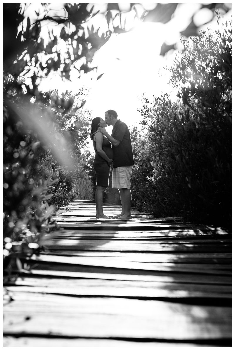 Husband and wife kissing on a beach boardwalk during maternity family phots in Playa Avellanas Costa Rica. Photographed by Kristen M. Brown, Samba to the Sea Photography.