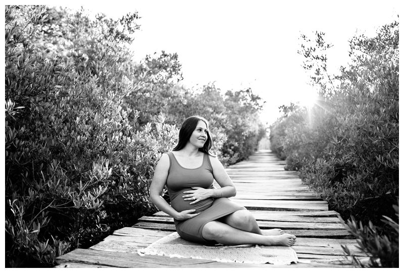 Pregnant woman on a beach boardwalk during maternity family phots in Playa Avellanas Costa Rica. Photographed by Kristen M. Brown, Samba to the Sea Photography.