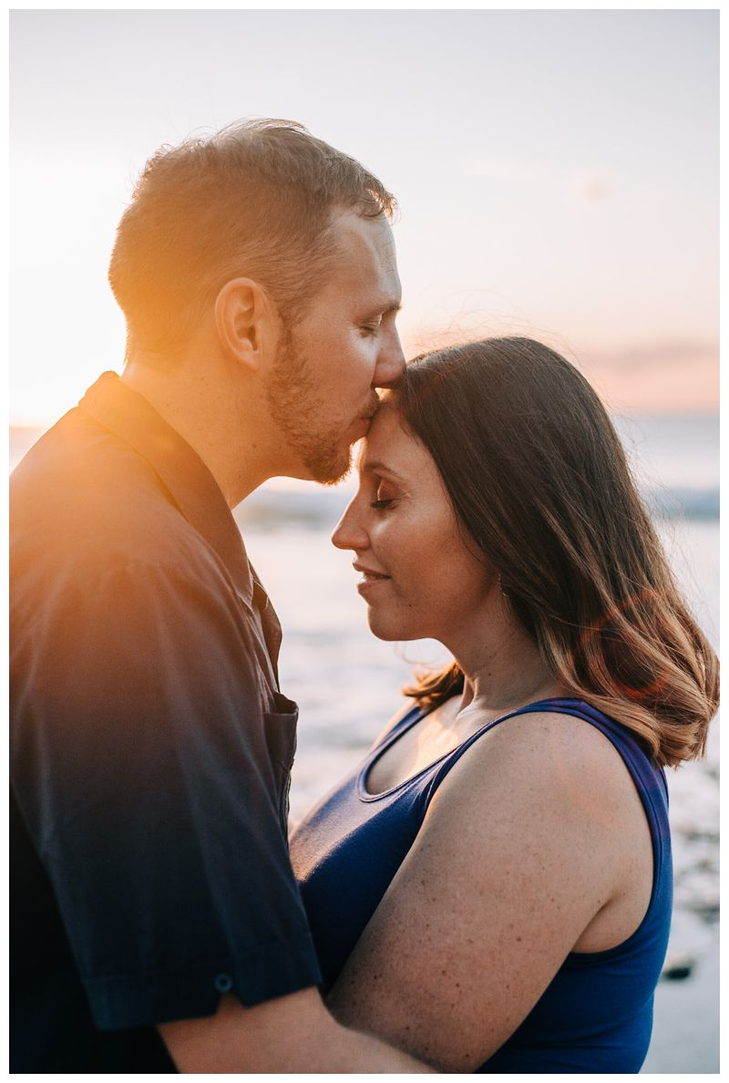Husband and wife kissing on the beach during maternity family phots in Playa Avellanas Costa Rica. Photographed by Kristen M. Brown, Samba to the Sea Photography.