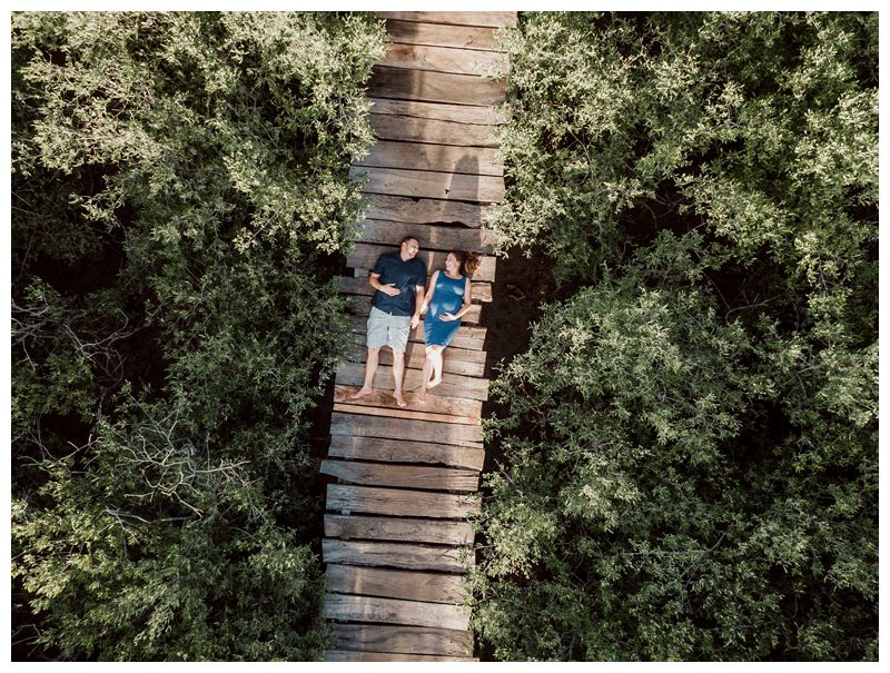 Aerial image of husband and wife laying a beach boardwalk during maternity family phots in Playa Avellanas Costa Rica. Photographed by Kristen M. Brown, Samba to the Sea Photography.