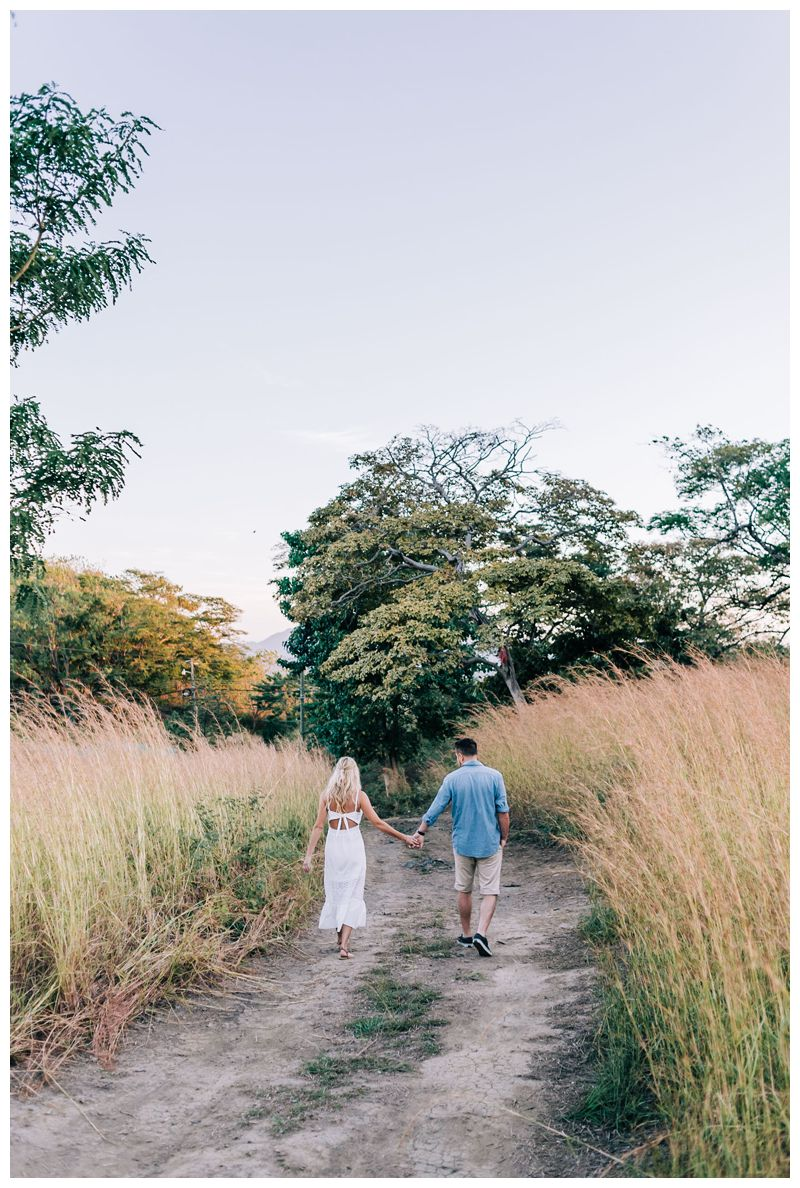 Couple holding hands walking during sunrise engagement photos in Tamarindo Costa Rica. Photographed by Kristen M. Brown, Samba to the Sea Photography.