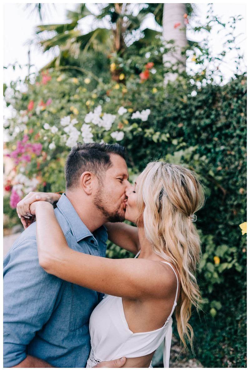 Couple romantically kissing in front of a flowering Bougainvillea bush during sunrise engagement photos in Tamarindo Costa Rica. Photographed by Kristen M. Brown, Samba to the Sea Photography.