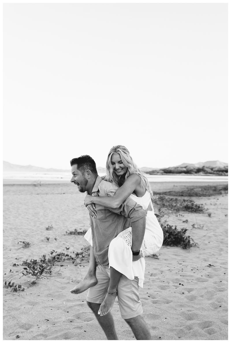 Boyfriend giving his girlfriend a piggy back ride during sunrise engagement photos in Tamarindo Costa Rica. Photographed by Kristen M. Brown, Samba to the Sea Photography.