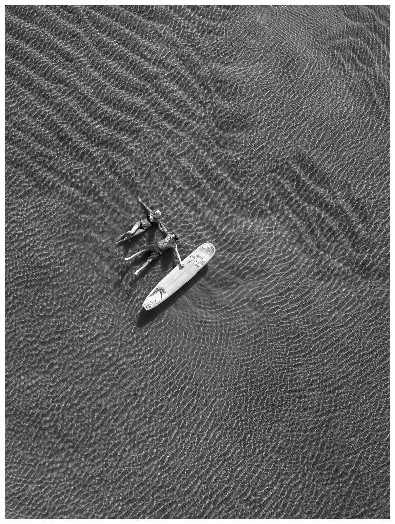 Aerial photo of surfer couple on the beach with a surfboard. Sunrise engagement photos in Tamarindo Costa Rica. Photographed by Kristen M. Brown, Samba to the Sea Photography.