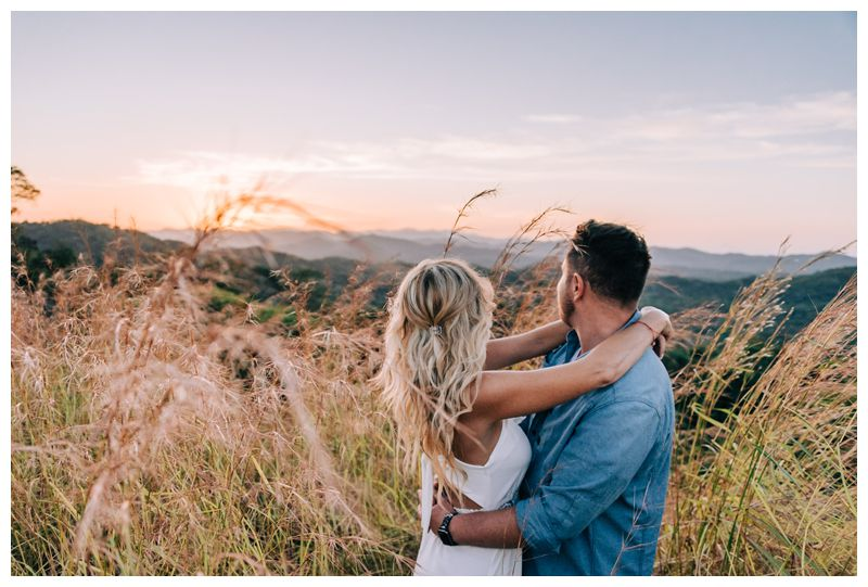Couple watching sunrise in between tall grass on a mountain during sunrise engagement photos in Tamarindo Costa Rica. Photographed by Kristen M. Brown, Samba to the Sea Photography.