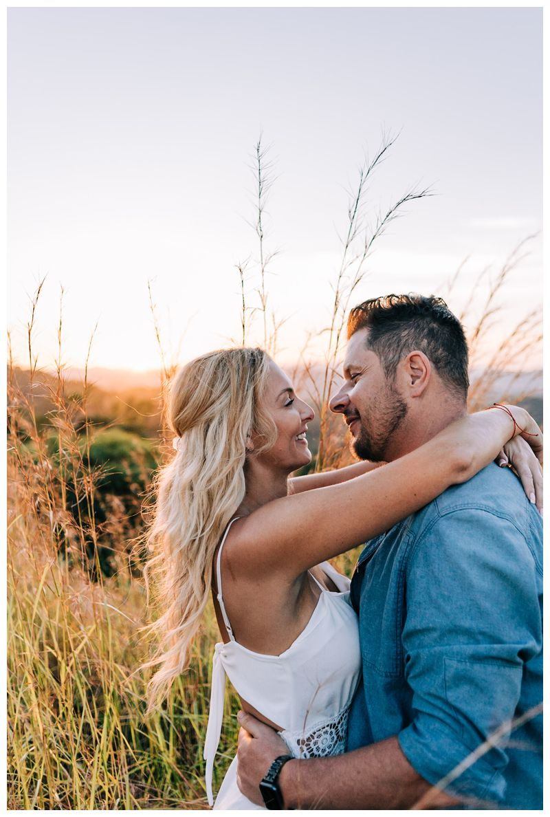 Couple kissing in between tall grass on a mountain during sunrise engagement photos in Tamarindo Costa Rica. Photographed by Kristen M. Brown, Samba to the Sea Photography.