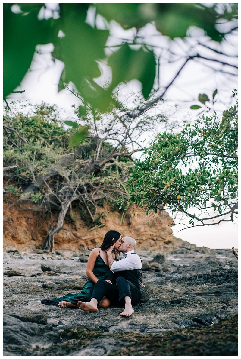 Husband and wife kissing on the beach during their tropical anniversary photos in Tamarindo Costa Rica. Photographed by Kristen M. Brown, Samba to the Sea Photography.