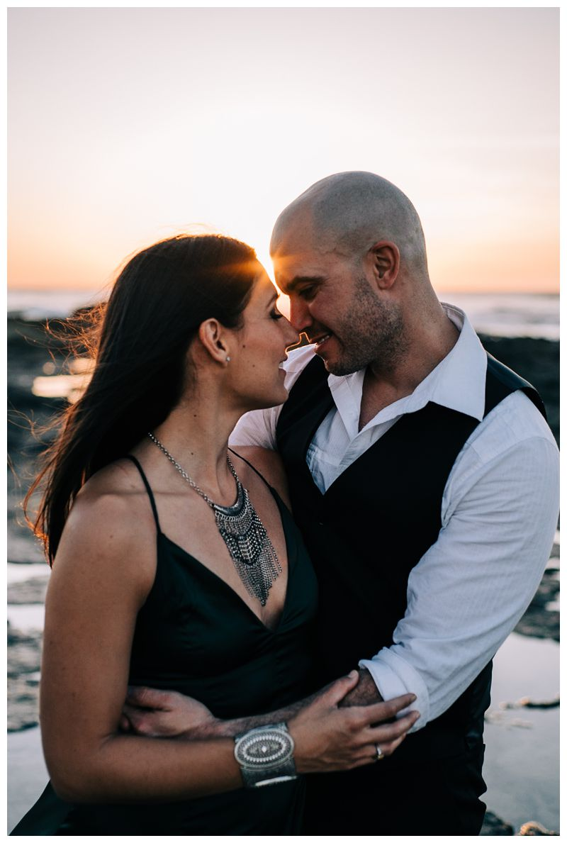 Husband and wife kissing on the beach during sunset during their tropical anniversary photos in Tamarindo Costa Rica. Photographed by Kristen M. Brown, Samba to the Sea Photography.
