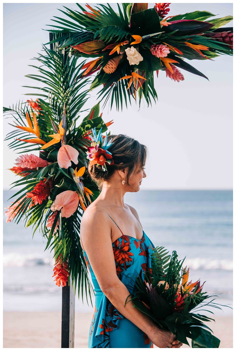 Bride standing in front of her tropical alter. Tropical wedding details with Mostera leaf, birds of paradise flower, and anthurium (Hawaiian Heart) florals. Tropical wedding in Tamarindo Costa Rica. Photographed by Kristen M. Brown, Samba to the Sea Photography.