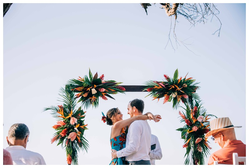 Bride and groom kissing in front of their tropical alter. Tropical wedding details with Mostera leaf, birds of paradise flower, and anthurium (Hawaiian Heart) florals. Tropical wedding in Tamarindo Costa Rica. Photographed by Kristen M. Brown, Samba to the Sea Photography.