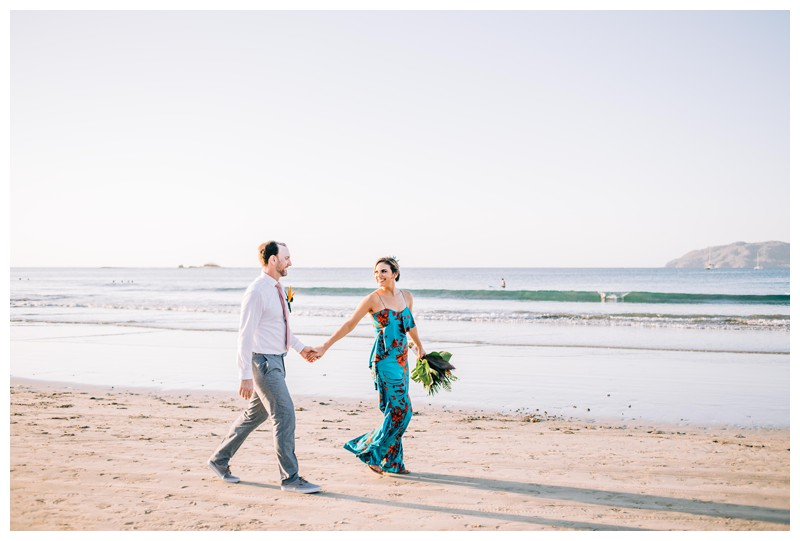 Bride and groom walking on the beach after their tropical wedding in Costa Rica. Photographed by Kristen M. Brown, Samba to the Sea Photography.