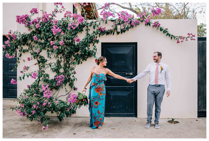 Bride and groom standing in front a magenta Bougainvillea after their tropical wedding in Costa Rica. Photographed by Kristen M. Brown, Samba to the Sea Photography.