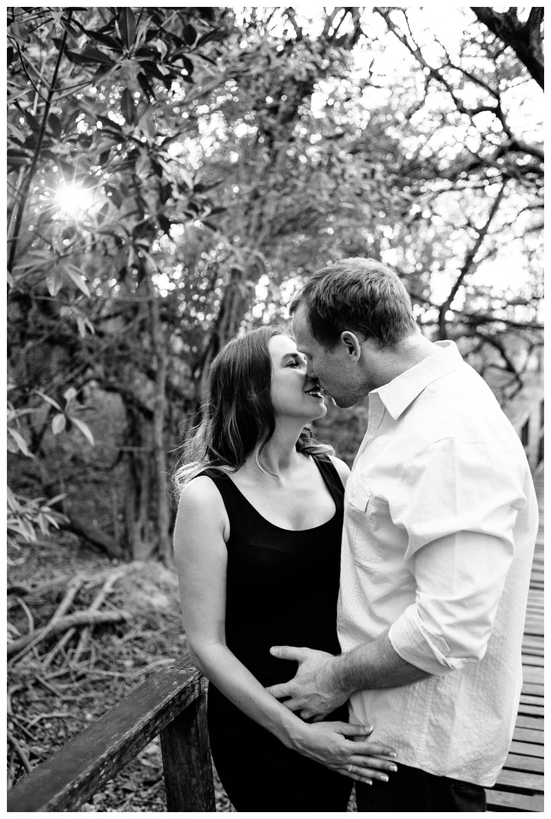 Couple kissing on a beach boardwalk path during beach maternity photos in Tamarindo Costa Rica. Photographed by Kristen M. Brown, Samba to the Sea Photography.
