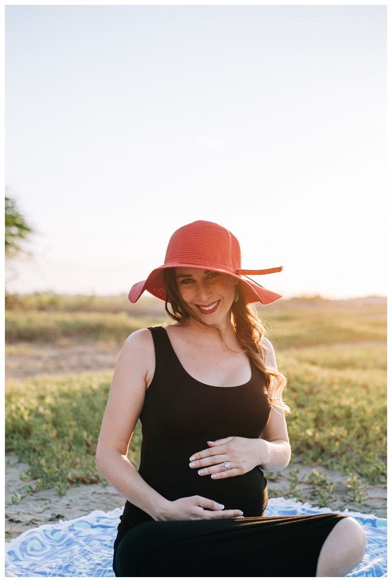 Glowing pregnant woman on the beach in a black dress and red hat for beach maternity photos in Tamarindo Costa Rica. Photographed by Kristen M. Brown, Samba to the Sea Photography.