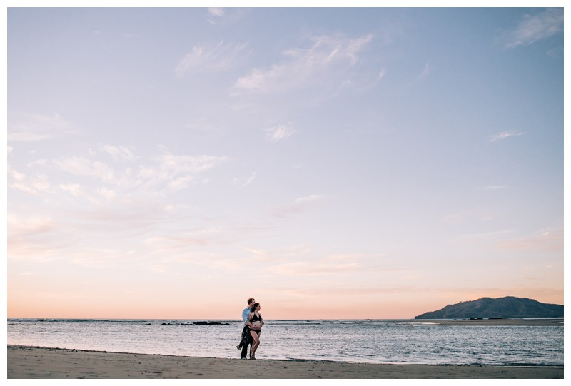Couple enjoying a pastel sunset during beach maternity photos in Tamarindo Costa Rica. Photographed by Kristen M. Brown, Samba to the Sea Photography.