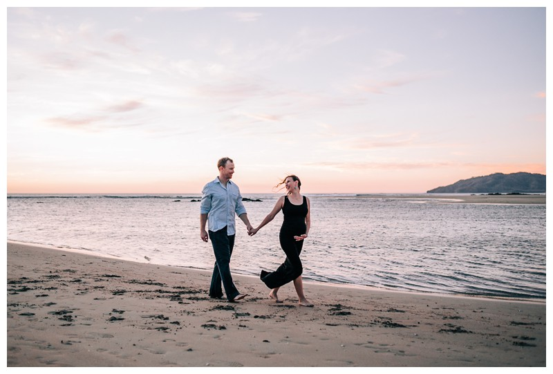 Husband and wife walking on the beach during beach maternity photos in Tamarindo Costa Rica. Photographed by Kristen M. Brown, Samba to the Sea Photography.