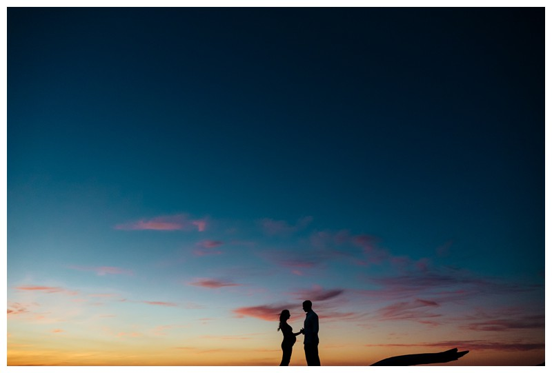 Couple taking in a beautiful sunset during beach maternity photos in Tamarindo Costa Rica. Photographed by Kristen M. Brown, Samba to the Sea Photography.