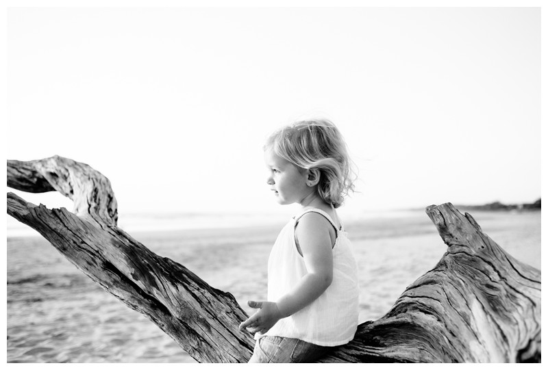 Little girl playing on driftwood tree during family photos in Playa Avellanas Costa Rica. Photographed by Kristen M. Brown, Samba to the Sea Photography.