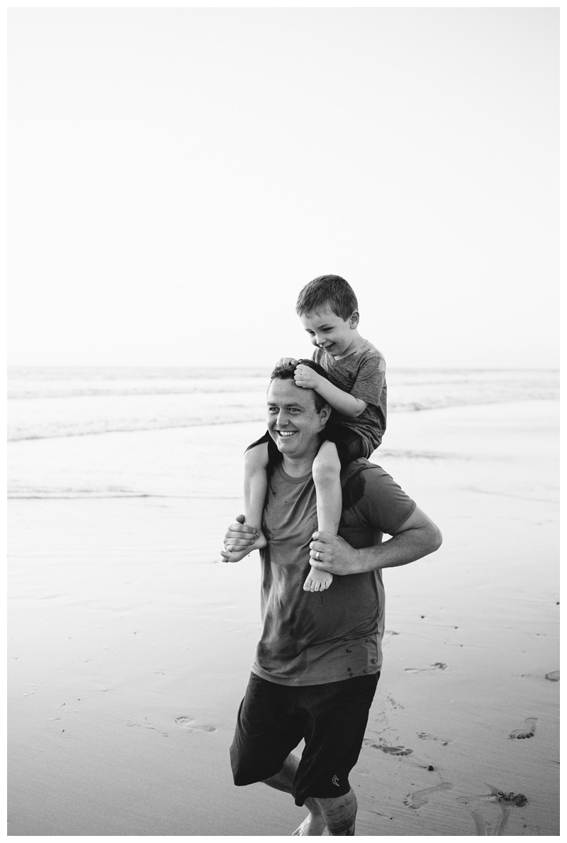 Dad giving his son a piggy back ride during family photos in Playa Avellanas Costa Rica. Photographed by Kristen M. Brown, Samba to the Sea Photography.