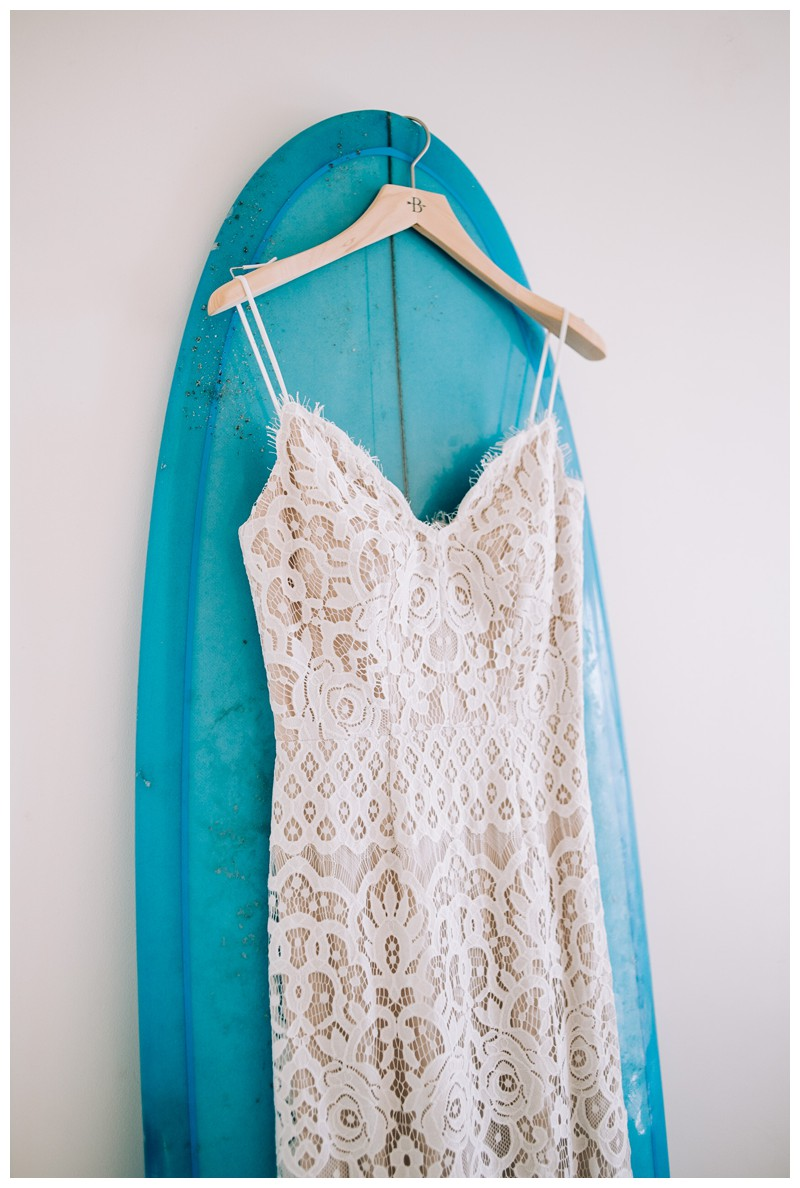 Wedding dress hanging on a turquoise surfboard. Photographed by Kristen M. Brown, Samba to the Sea Photography.