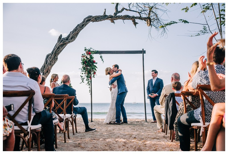 Bride + groom's first kiss at their destination beach wedding in Tamarindo Costa Rica. Photographed by Kristen M. Brown, Samba to the Sea Photography.