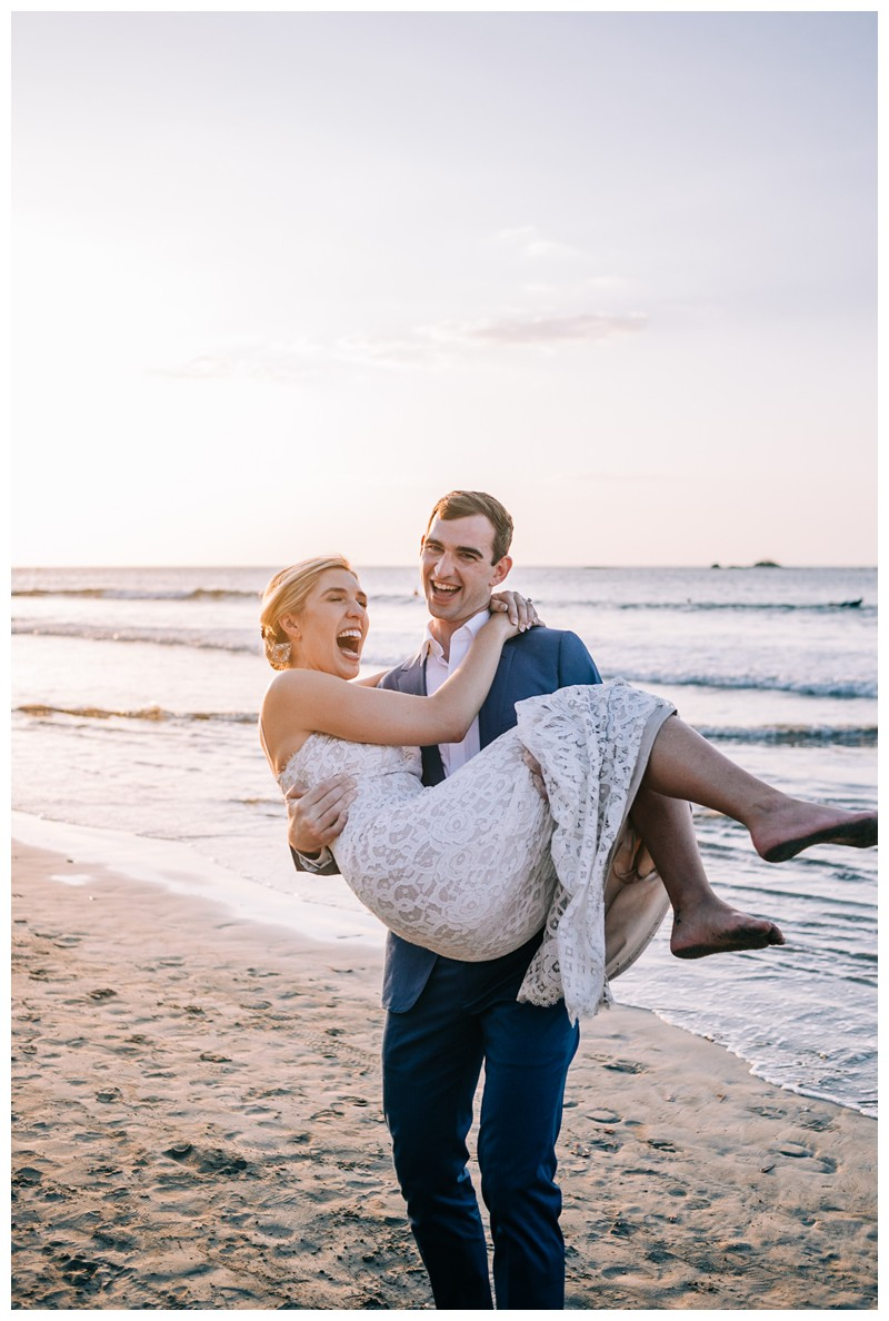 Groom carrying his bride on the beach after their destination beach wedding in Tamarindo Costa Rica. Photographed by Kristen M. Brown, Samba to the Sea Photography.