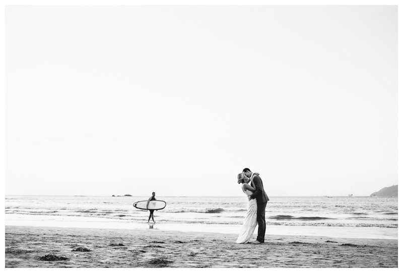 Bride and groom kissing on the beach as a surfer walks behind them after their destination beach wedding in Tamarindo Costa Rica. Photographed by Kristen M. Brown, Samba to the Sea Photography.