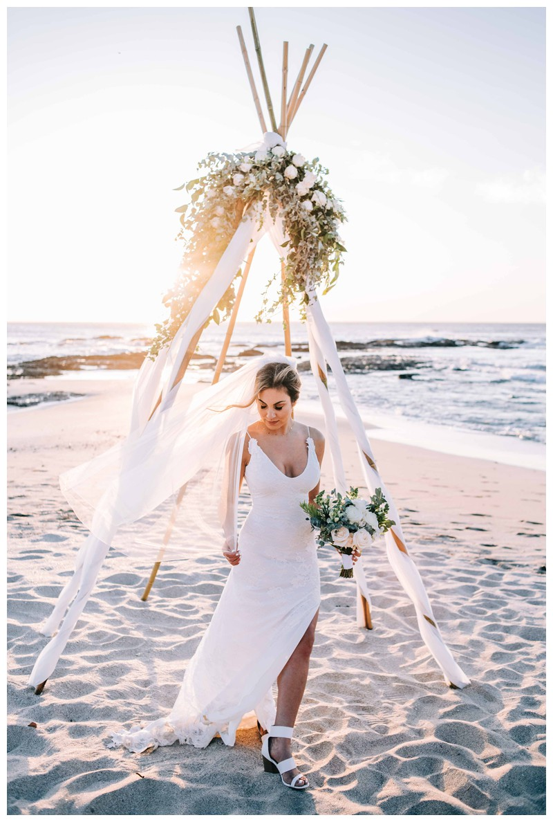 Bridal portrait in front of their tee pee floral alter on the beach. Elegant boho elopement in Costa Rica on the beach in Playa Langosta. Photographed by Kristen M. Brown, Samba to the Sea Photography.