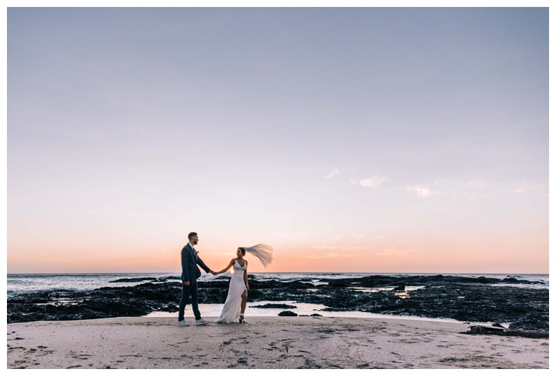 Bride and groom on the beach during sunset after their elegant boho elopement in Costa Rica on the beach in Playa Langosta. Photographed by Kristen M. Brown, Samba to the Sea Photography.