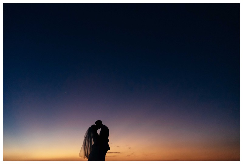 Bride and groom kissing on the beach during sunset after their elegant boho elopement in Costa Rica on the beach in Playa Langosta. Photographed by Kristen M. Brown, Samba to the Sea Photography.
