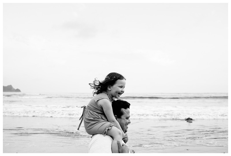 Dad giving his little girl a piggy back ride during family photos in Playa Guiones Costa Rica. Photographed by Kristen M. Brown, Samba to the Sea Photography.