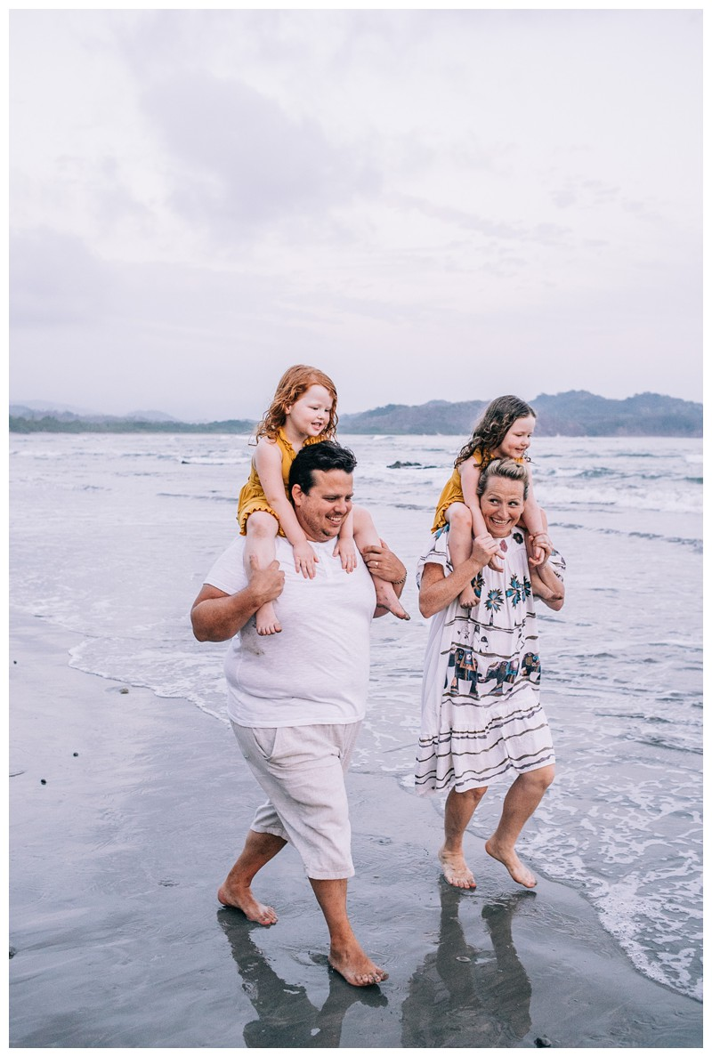 Mom and dad giving their little girls piggy back rides during family photos in Playa Guiones Costa Rica. Photographed by Kristen M. Brown, Samba to the Sea Photography.