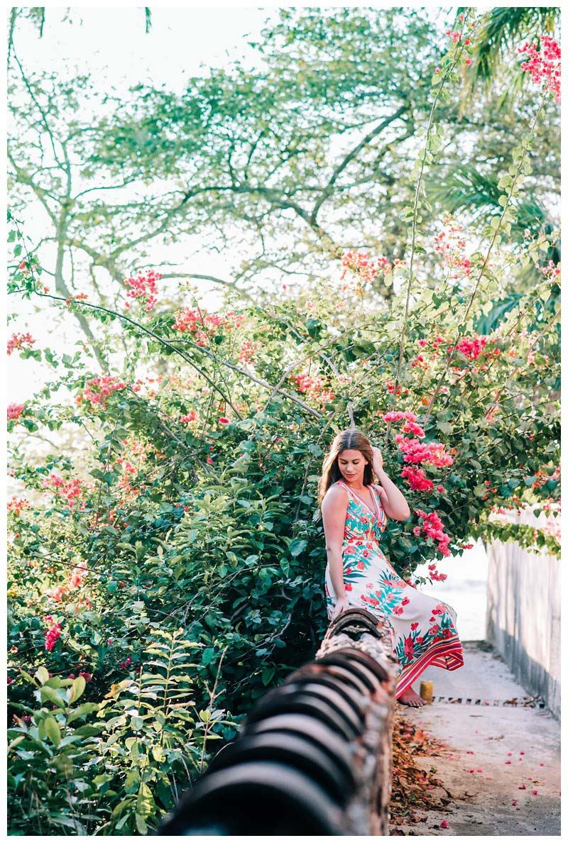 Young woman sitting on a wall in front a gorgeous magenta Bougainvillea bush. Senior year lifestyle photos in Playa Flamingo Costa Rica. Photographed by Kristen M. Brown, Samba to the Sea Photography.