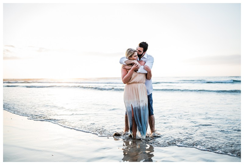 Husband and wife embracing on the beach in Tamarindo Costa Rica. Photographed by Kristen M. Brown, Samba to the Sea Photography.