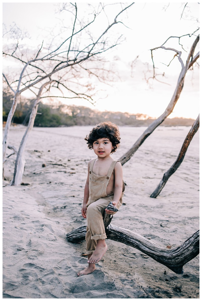 Portrait of little boy sitting on a driftwood tree in Tamarindo. Family photos at Hotel Capitan Suizo in Tamarindo Costa Rica. Photographed by Kristen M. Brown, Samba to the Sea Photography.