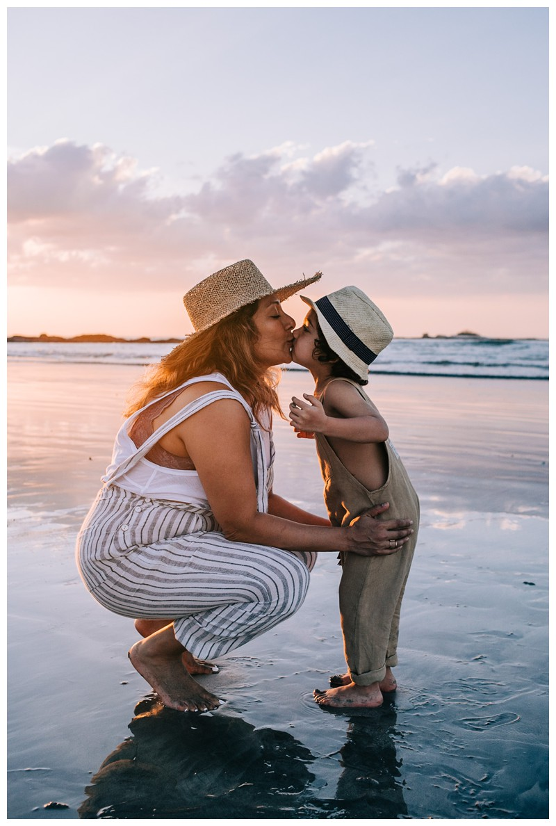 Little boy giving his mom a kiss on the beach during sunset in Tamarindo Costa Rica. Family photos at Hotel Capitan Suizo in Tamarindo Costa Rica. Photographed by Kristen M. Brown, Samba to the Sea Photography.