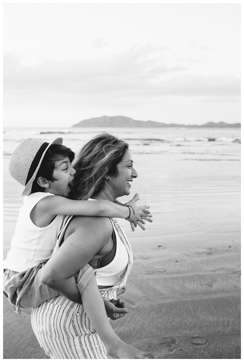 Mom giving her son a piggy back ride on the beach during sunset in Tamarindo Costa Rica. Family photos at Hotel Capitan Suizo in Tamarindo Costa Rica. Photographed by Kristen M. Brown, Samba to the Sea Photography.