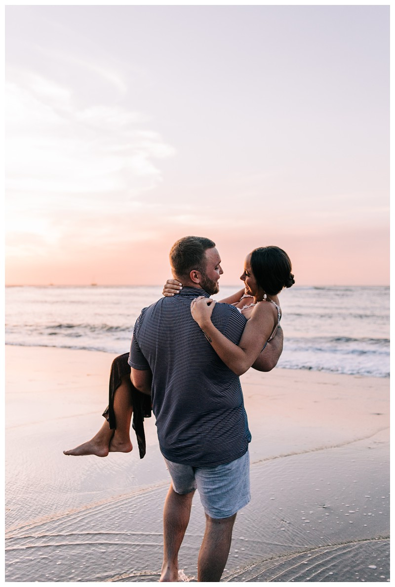 Boyfriend carrying his fiancé on the beach after a golden hour beach proposal in Tamarindo Costa Rica. Photographed by Kristen M. Brown, Samba to the Sea Photography.