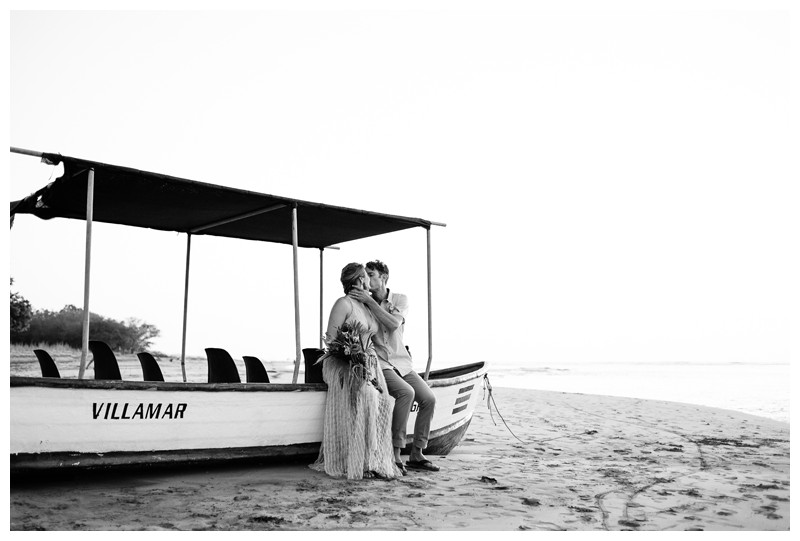 Bride and groom kissing on the beach on a Panga Boat in Tamarindo Costa Rica during golden hour. Intimate destination beach wedding in Costa Rica. Photographed by Kristen M. Brown, Samba to the Sea Photography.