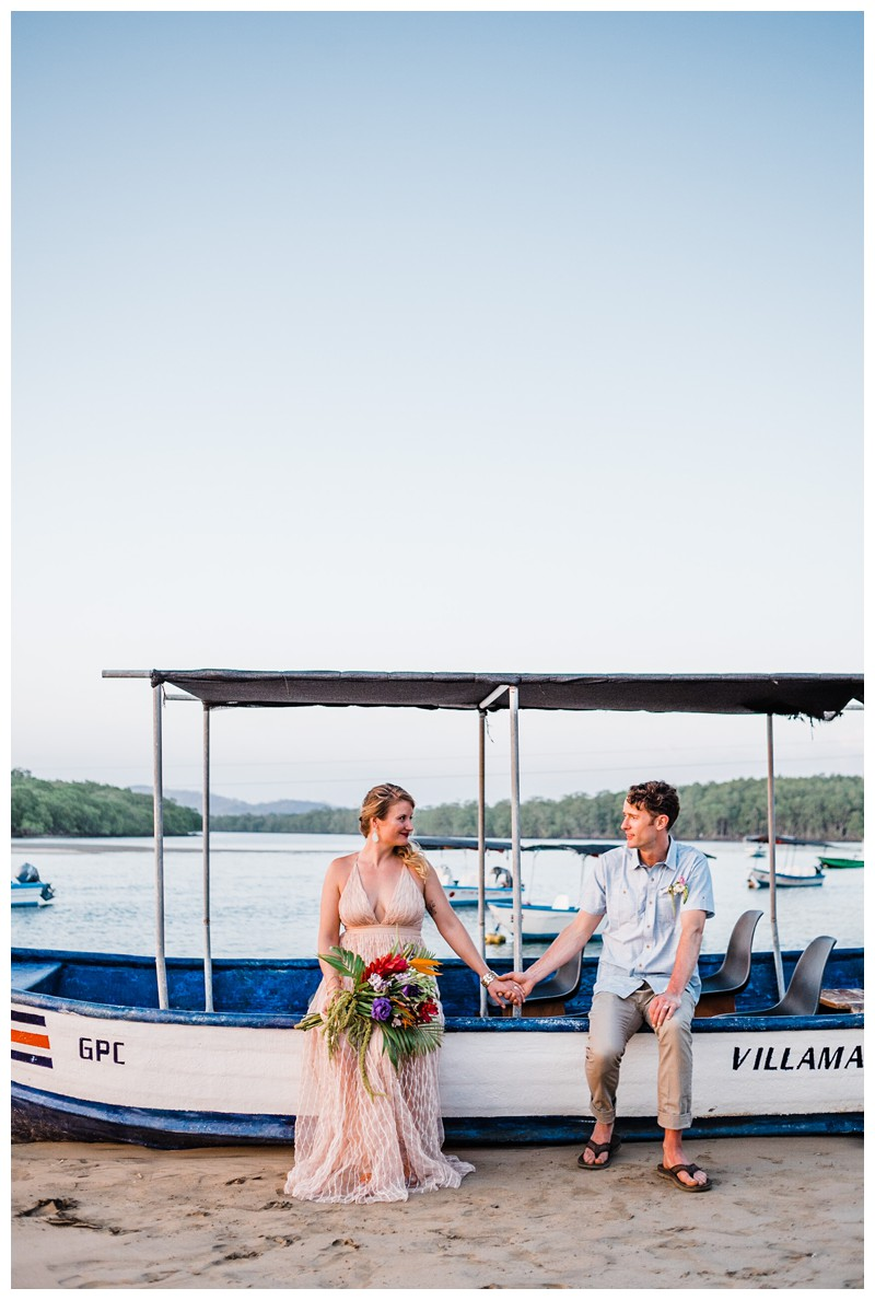 Bride and groom sitting on on a Panga boat in Tamarindo Costa Rica during golden hour. Intimate destination beach wedding in Costa Rica. Photographed by Kristen M. Brown, Samba to the Sea Photography.