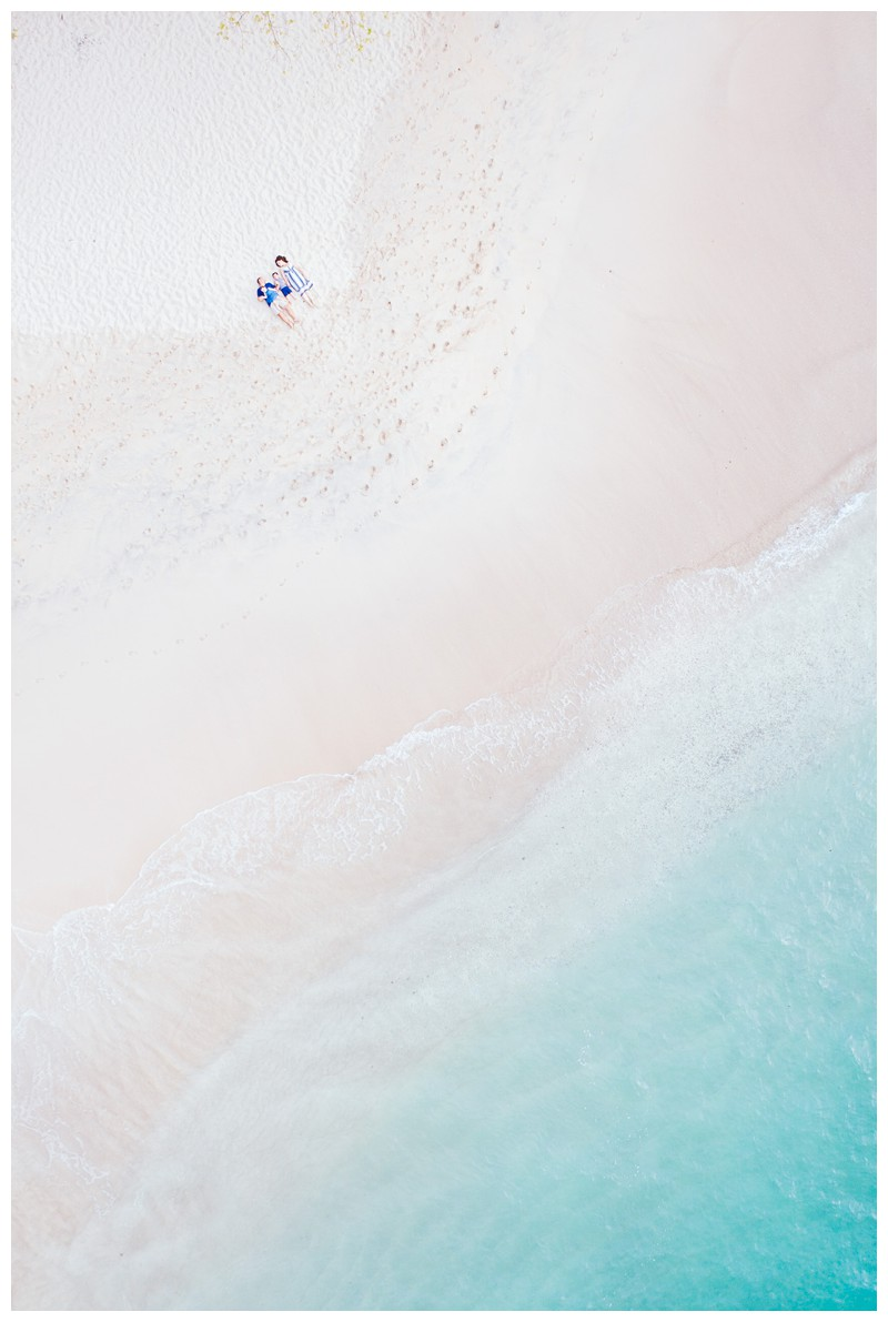 Aerial photo of family laying in the sand with turquoise water. Beach family photos in Playa Conchal Costa Rica. Photographed by Kristen M. Brown, Samba to the Sea Photography. Beach lifestyle photos in Costa Rica. Photographed by Kristen M. Brown, Samba to the Sea Photography.