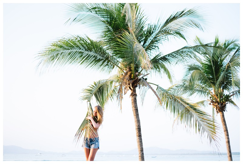 Woman embracing a palm tree frond on the beach in Tamarindo Costa Rica. Beach lifestyle photos in Costa Rica. Photographed by Kristen M. Brown, Samba to the Sea Photography.