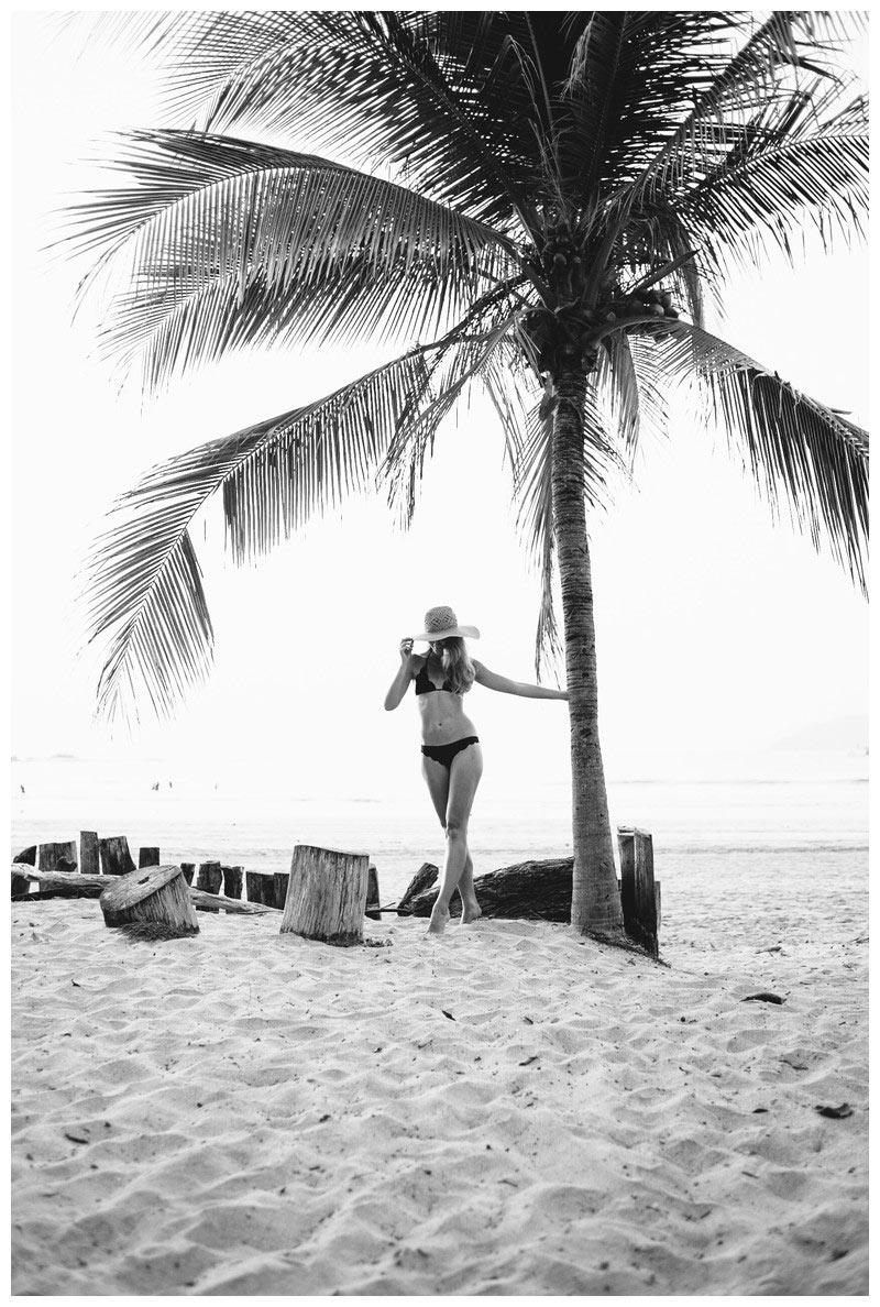 Portrait of a woman and a palm tree on the beach in Tamarindo Costa Rica. Beach lifestyle photos in Costa Rica. Photographed by Kristen M. Brown, Samba to the Sea Photography.
